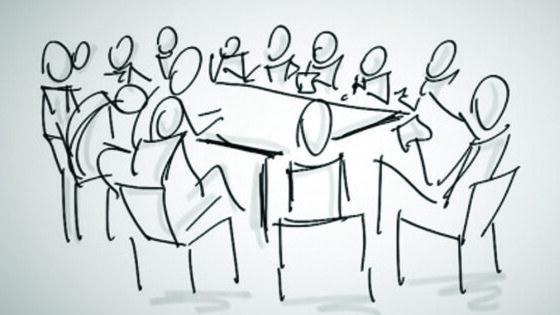 leden zitten aan tafel te discussieren